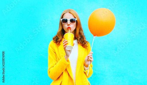 Photo  Fashion woman drinks fruit juice holds an orange air balloon on colorful blue ba