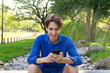 Outside portrait of young man in park. Smiling handsome teenager typing or reading at phone