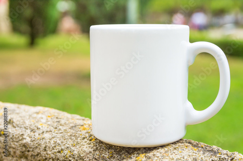 White mockup coffee or tea mug on standing on stone outdoors. Nature background with green trees grass. Summer spring. Blank space for ext artwork lettering