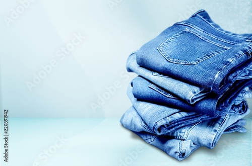 Tela  Pile of blue jeans over white background