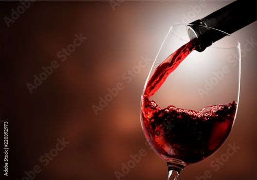 Staande foto Wijn Red wine pouring in glass on background