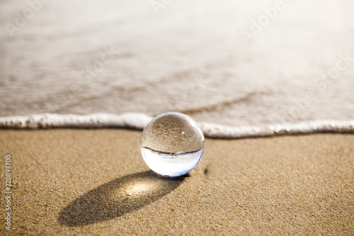 Staande foto Stenen in het Zand glass ball crystal clear reflecting the sea and beach in the morning