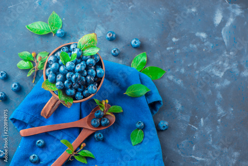 Fotobehang Schilderkunstige Inspiratie Handmade ceramic cup with blueberries. Ripe and sweet summer berries on a concrete background. Natural beauty, blue and gray palette, copy space
