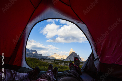 Fotobehang Kamperen Bivouac at Tre Cime di Lavaredo, family resting in tent, red illuminated tent on pass in Dolomites, Italy