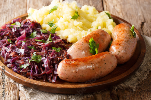 Roasted sausages with red sauerkraut and potatoes close-up on a plate on a table. horizontal