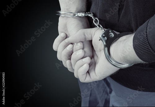 Arrested man in handcuffs hith hands behind back Wallpaper Mural