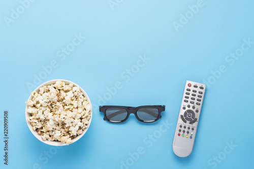 Photo  Bowl with popcorn, Imax glasses, remote control for TV on a blue