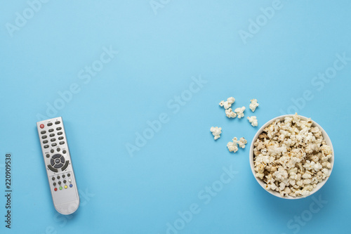 Photo  Bowl with popcorn and remote control for TV on a blue background