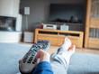 Eine kindliche Hand hält eine moderne Fernbedienung und zeigt damit auf den Fernseher. Die Füße liegen auf einem Sofa