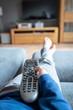 Eine kindliche Hand hält eine moderne Fernbedienung und zeigt damit auf den Fernseher. Die Füße liegen auf der Couch