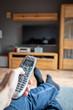 Eine männliche Hand hält eine moderne Fernbedienung und zeigt damit auf den Fernseher. Die Füße liegen auf der Couch