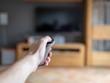 Eine männliche Hand hält eine moderne Fernbedienung und zeigt damit auf den Fernseher