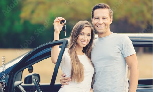 Young happy couple standing by car smiling - concept of buying