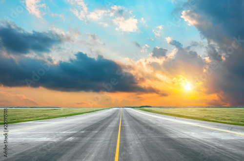 Asphalt road with a dividing strip of yellow at dawn in the early morning. - 220915118