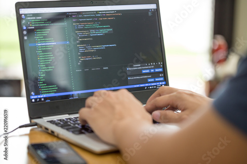 Fototapeta Freelance programmer or developer working at home and typing source code with laptop obraz