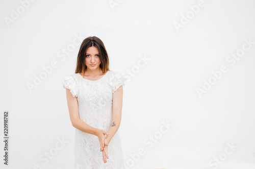 Fotografie, Obraz  Portrait of beautiful insidious woman in white dress looking at camera