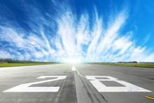 Airport Runway To In Horizon And Picturesque Cirrus Clouds In The Blue Sky.
