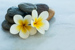 Spa set with flower and stones on white marble table outdoors