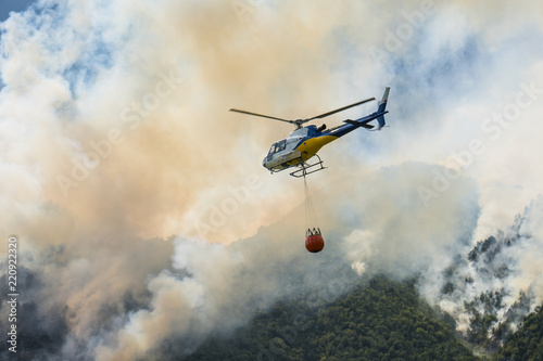 Foto op Plexiglas Helicopter Aerial firefighting with helicopter on a big wildfire in a pine forest
