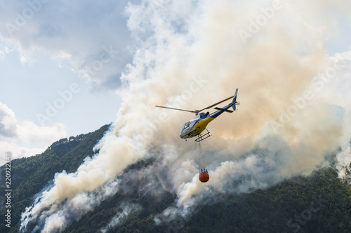 Foto op Canvas Helicopter Aerial firefighting with helicopter on a big wildfire in a pine forest
