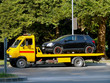 Black car is loaded on a yellow car tow truck on a city street on a summer day