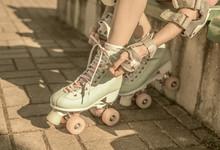 Skater Girl Putting On Mint Retro Roller Skates Outdoor
