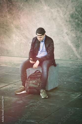 Photo Conceptual image about the alienation of young contemporary people: a lonely boy sitting on a bench watching with his eyes off his smartphone