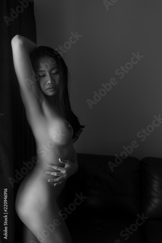 Low key artistic nude of young sexy Asian woman leaning on window in the living room in black and white
