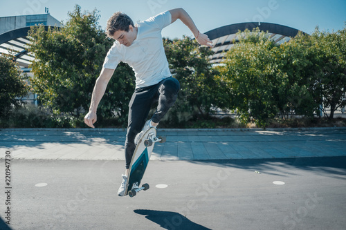Fotografie, Obraz  Young attractive man riding and jumping longboard in the park.