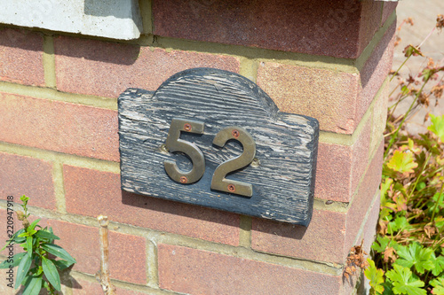 Photo  House number 52 sign on red brick wall