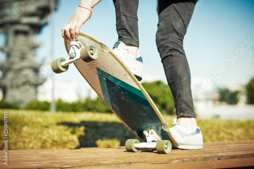 Close up of young man riding longboard or skateboard in the park.