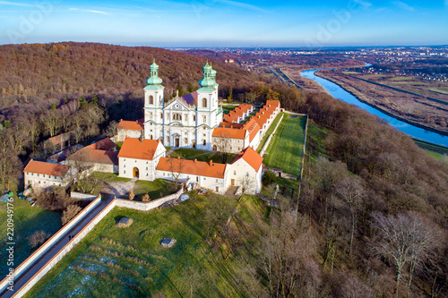 Fototapeta Krakow, Poland. Camaldolese Monastery and church in the wood on the hill in Bielany, Krakow, near Tyniec. Aerial view with Vistula River and far view of Cracow city in the background obraz