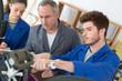 Student using spanner, teacher observing