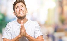 Young Handsome Man Over Isolated Background Begging And Praying With Hands Together With Hope Expression On Face Very Emotional And Worried. Asking For Forgiveness. Religion Concept.