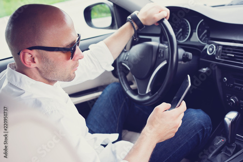 Vászonkép  Young man texting and driving
