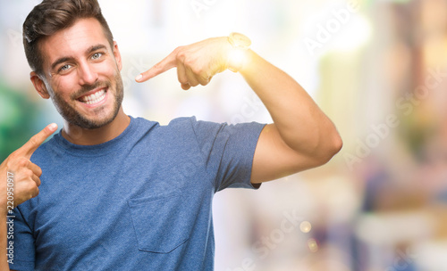 Foto Young handsome man over isolated background smiling confident showing and pointing with fingers teeth and mouth