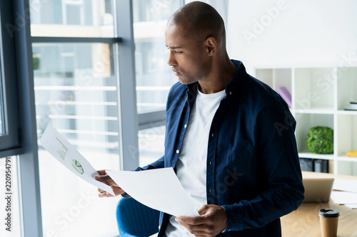 Fotografie, Obraz  Successful African entrepreneur studying documents with attentive and concentrated look, drinking coffee at cafe