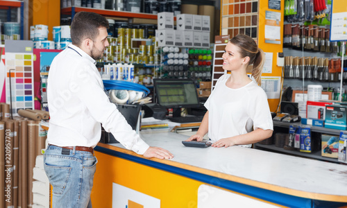Fotografía  Cheerful girl seller helping  male customer  at the counter