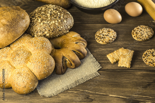 Food. Baking bread. Fresh bread baked in a bakery, biscuits, chicken eggs and flour on the background of a wooden table texture