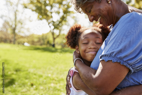 Photo Close Up Of Granddaughter Hugging Grandmother In Park