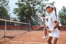 Great Teamwork On Court! Side View Of Sporty Beautiful Woman And Girl Playing Tennis In Team Outdoors. Sporty Family Standing Together By One Side On Tennis Court. Sport Team