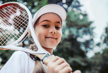 Tennis Training For Young Kid Outdoors. Portrait Of Happy Sporty Little Girl On Tennis Court. Caucasian Child In White Tennis Sportswear On Training. Sporty Child Girl Looking In The Camera.