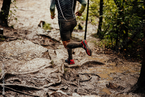 Fotografía  dirty feet runner in compression socks running on trail in woods