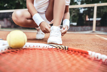 Girl On Tennis Court In The Sport Club. Cropped Image Of A Little Tennis Player. Girl Child Tying Shoelaces On Tennis Court. Summer Activities For Children.