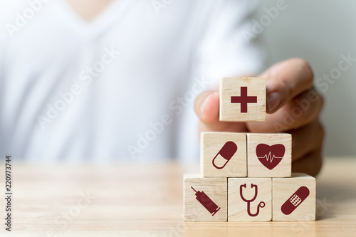 Fototapeta Hand arranging wood block stacking with icon healthcare medical, Insurance for your health concept obraz