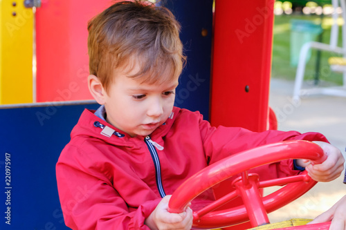 Boy playing on playground car carousel in the amusement park