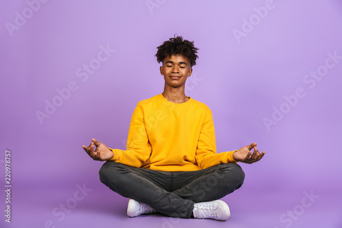 Obraz Portrait of relaxed african american boy sitting in lotus pose and meditating with closed eyes, isolated over violet background - fototapety do salonu