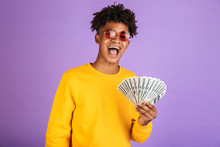 Portrait Of Fashion African American Man Wearing Sunglasses Smiling While Holding Cash Money Dollars, Isolated Over Violet Background