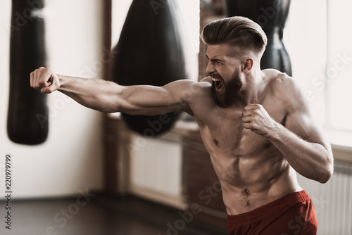 Foto  Athletic Male Boxer Training at Boxing studio