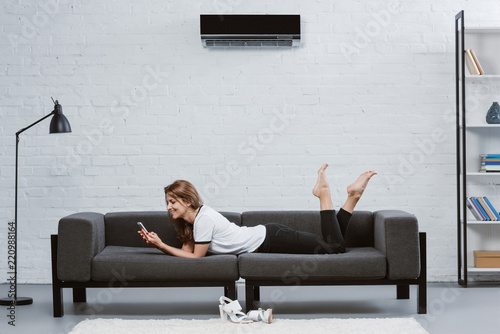 Fototapeta happy young woman using smartphone while lying on sofa under air conditioner hanging on wall obraz